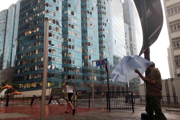 Les fenêtres endommagées de la tour de bureaux One Harbourfront à Hongkong, le 16 septembre.Dès que les vents se sont calmés dimanche soir, la protection civile a multiplié les sorties pour commencer à déblayer les rues.