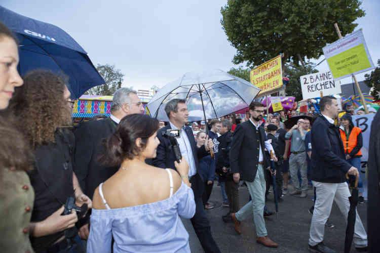 Markus Söder traverse un groupe de manifestants opposés à la construction d'une troisième piste d'atterrissage à Munich, avant de rejoindre son meeting.