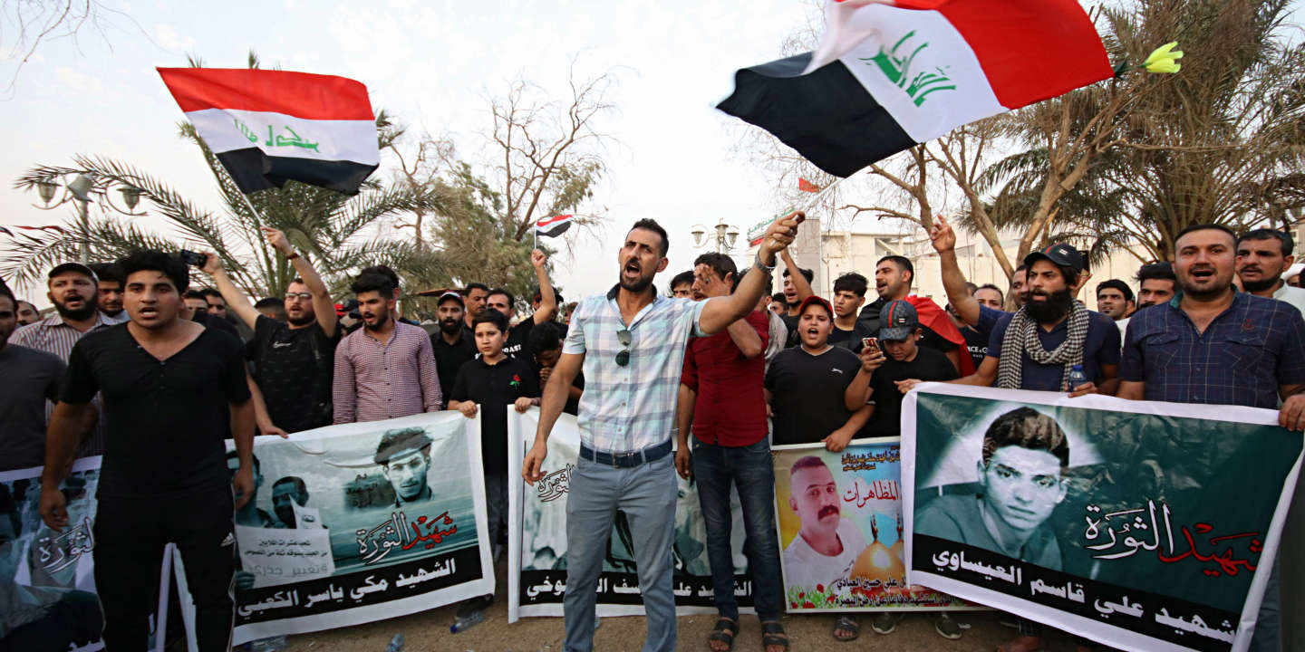 Demonstrators hold national flags and images of protesters who were killed during previous demonstrations, demanding better public services and jobs, in Basra, Iraq, Wednesday, Sept. 12, 2018. (AP Photo/Nabil al-Jurani)