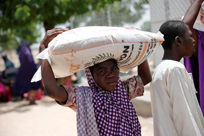 Une femme porte un sac de riz distribué par une ONG dans le camp de réfugiés de Maiduguri, dans le nord-est du Nigéria, en juin 2017.