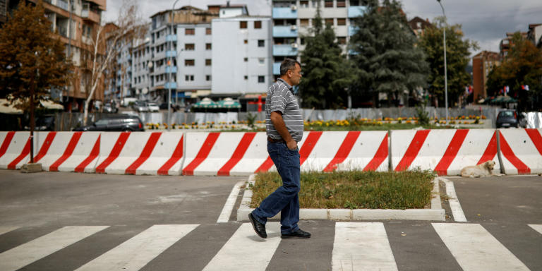 FILE PHOTO: A man walks past a concrete barrier at the end of a main bridge over the river Ibar in Mitrovica, Kosovo, September 5, 2018. Picture taken September 5, 2018. REUTERS/Marko Djurica/File Photo