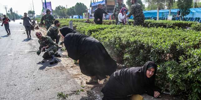 This picture taken on September 22, 2018 in the southwestern Iranian city of Ahvaz shows Iranian women and soldiers taking cover next to bushes at the scene of an attack on a military parade that was marking the anniversary of the outbreak of its devastating 1980-1988 war with Saddam Hussein's Iraq. Dozens of people were killed with dozens others wounded in an attack in the southwestern Khuzestan province on September 22 targeting on an army parade commemorating the anniversary of the 1980-1988 Iran Iraq war, state media reported. / AFP / ISNA / MORTEZA JABERIAN