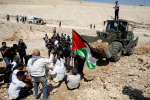 Des Palestiniens se regroupent devant un bulldozer israéliens pour protester contre le plan de démolition du village de Khan Al-Ahmar, en Cisjordanie occupée, 14 septembre 2018.