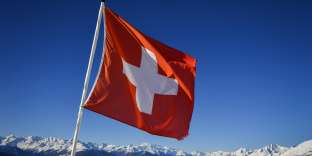 """A Swiss flag flutters on March 4, 2018 in Crans-Montana above the Rhone valley in the Swiss canton of Valais, location of Sion, a city of some 34,000 souls bidding to host the 2026 Winter Olympic Games. The official race to succeed 2018 hosts Pyeongchang, and Beijing in 2022 begins in March when would be candidates file """"letters of intention"""" to the International Olympic Committee. / AFP PHOTO / Fabrice COFFRINI"""