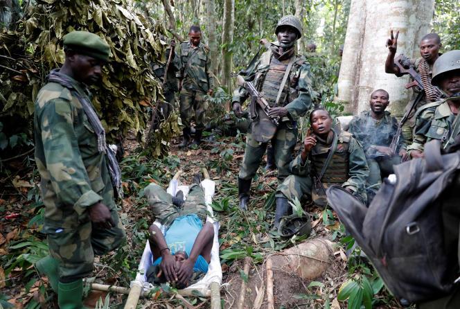 Des membres des forces armées de la République démocratique du Congo (FARDC) entourent l'un des leurs, blessé, après avoir pris le contrôle d'un camp du groupe d'origine ougandaise ADF, auNord-Kivu, le 19 février 2018.