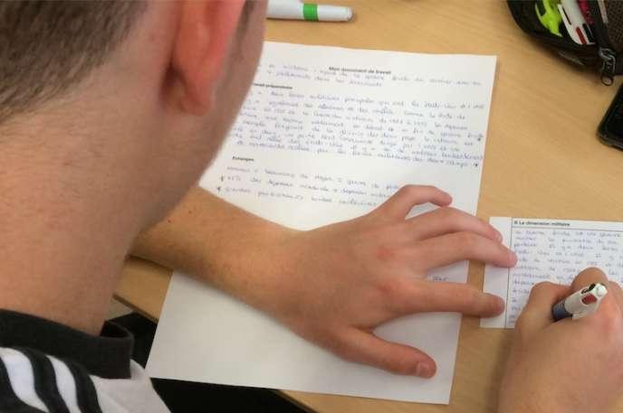 Elève en train de rédiger son texte dans le cadre d'un groupe puzzle au lycée Jules-Haag, à Besançon.