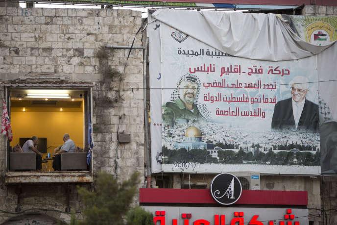 Des Palestiniens dans un café à Naplouse, à côté d'une affiche de Yasser Arafat et Mahmoud Abbas, le 27 septembre.
