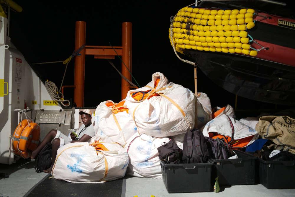 Mohamed, adossé aux gilets de sauvetage rangés dans des sacs. La veille au soir, ce jeune Libyen de 14 ans a quitté son pays et la ville de Zouara sur un bateau de pêcheur avec sa famille et 47 personnes à bord. L'équipage de SOS Méditerranée leur est venu en aide dans la nuit du 22 au 23 septembre et s'est assuré de leur prise en charge avec MSF après une longue négociation mouvementée avec les gardes-côtes de Tripoli.
