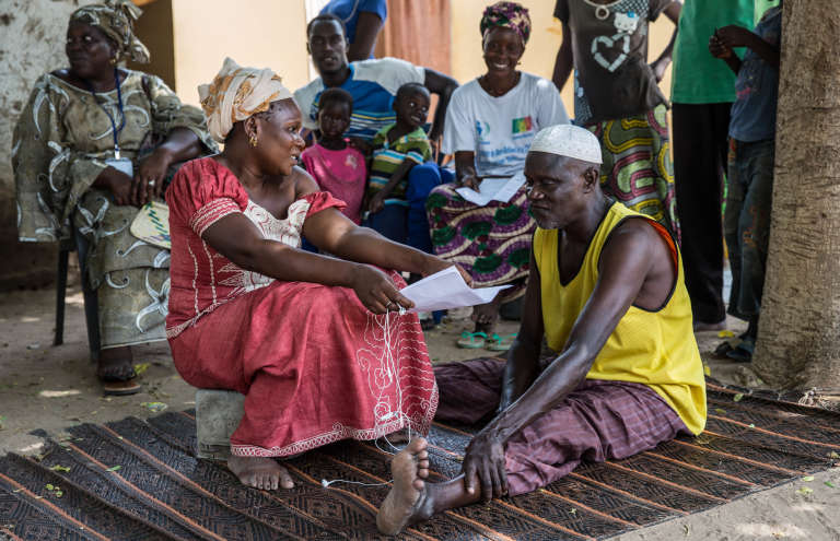 Marcelle Thiombane, « relais» de la campagne nationale de lutte contre la tuberculose, discute, enseptembre 2018, avec un ancien «cas manquant» qu'elle a trouvé dans son village du département de Tivaouane, au Sénégal.