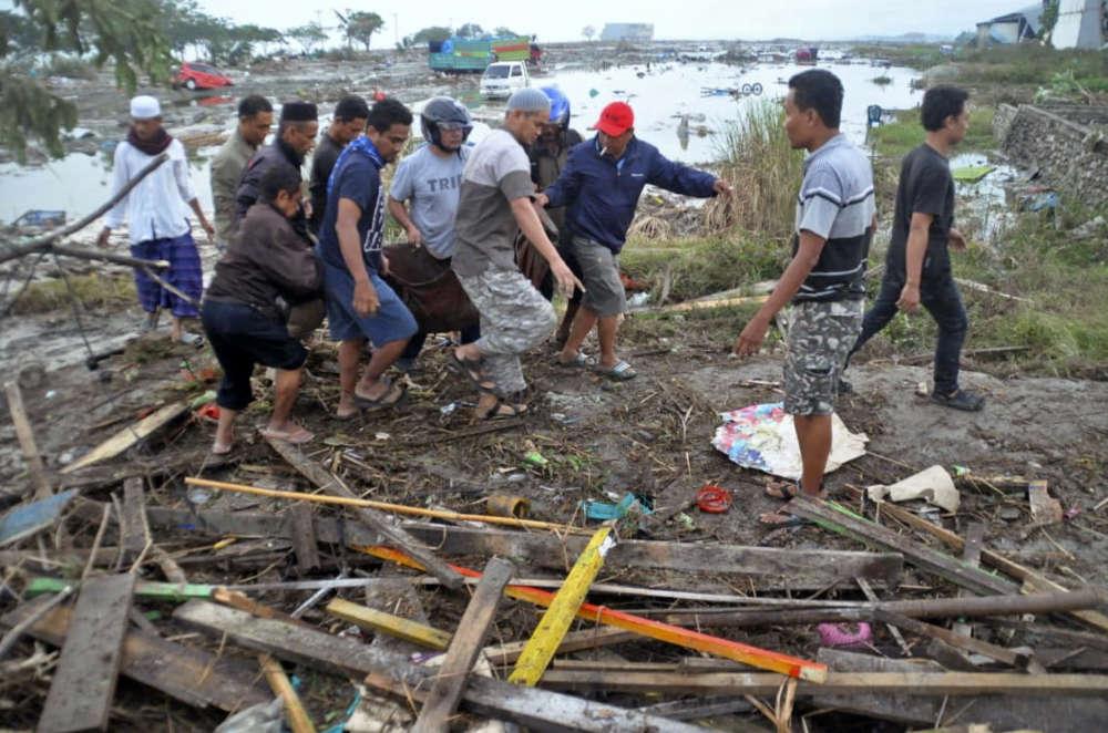 Les habitants de Palu transportent un corps, le 29 septembre.