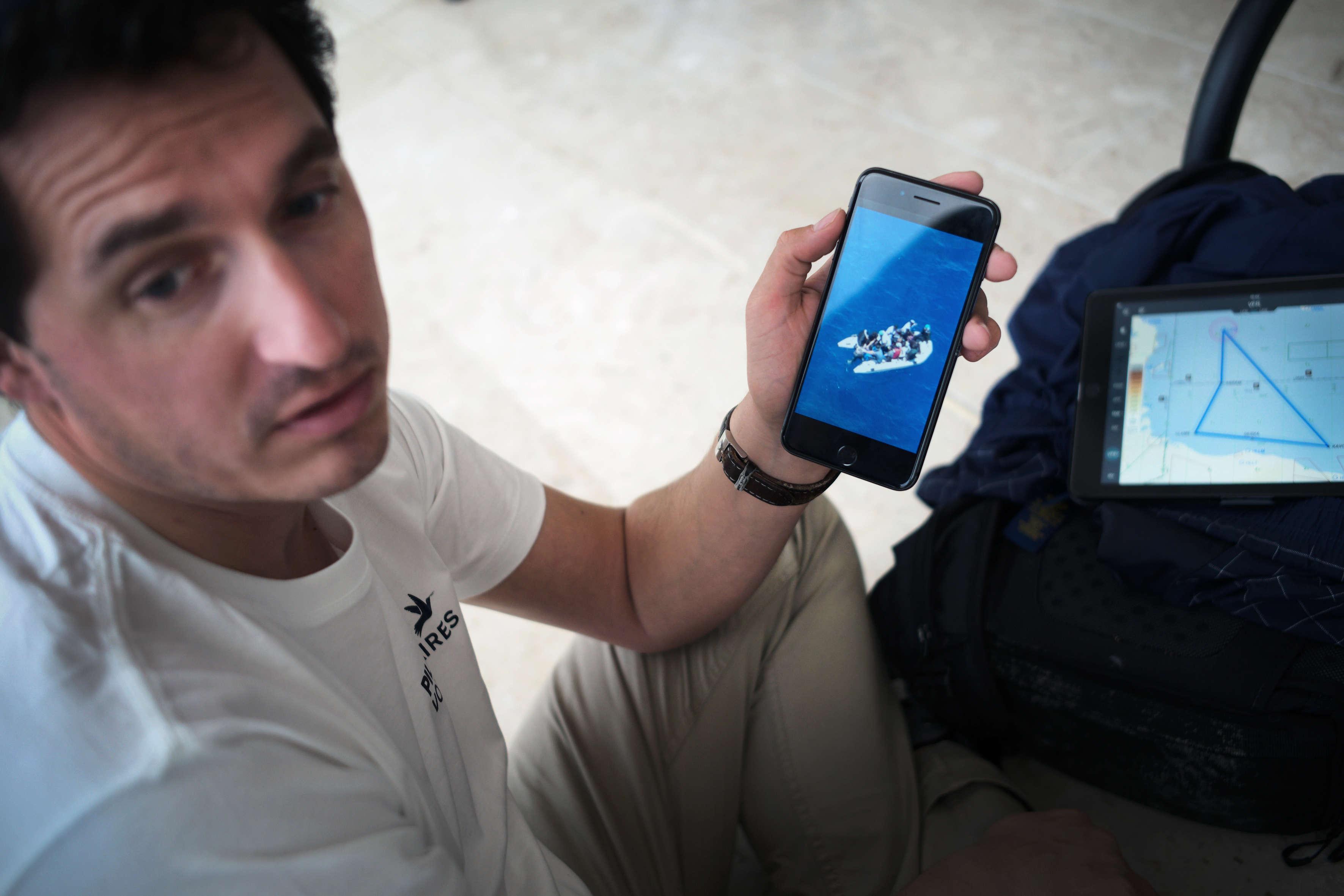 Benoît Micolon, cofondateur de l'ONG Pilotes volontaires, montre sur son téléphone une photo qu'il a prise en juin 2018 lors d'une mission de recherche de personnes en détresse en mer Méditerranée. En arrière-plan sa tablette qui lui permet de naviguer et suivre son plan de vol.