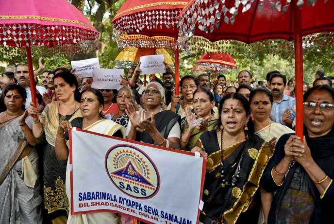 Des Indiennes tiennent des parapluies décoratifs utilisés pour les processions du temple hindou d'Ayyappa à Sabarimala, pour protester contre le récent verdict rendu par la Cour suprême à New Delhi, en Inde, le dimanche 7 octobre 2018. Le temple historique de Sabarimala avait empêché les femmes en âge de menstruer de pénétrer dans le temple.