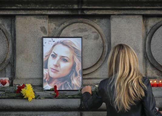 Une femme dépose une rose devant le portrait de la journaliste assassinée Viktoria Marina, devant le monument de la liberté, à Ruse, en Bulgarie le 8 octobre.