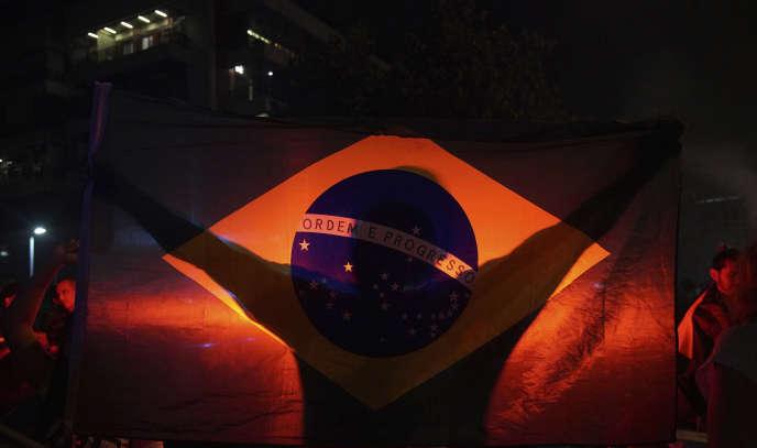 Un homme brandit un drapeau du Brésil à l'annonce du résultat du premier tour de l'élection présidentielle, donnant Jair Bolsonaro vainqueur, le 7 octobre à Rio de Janeiro.