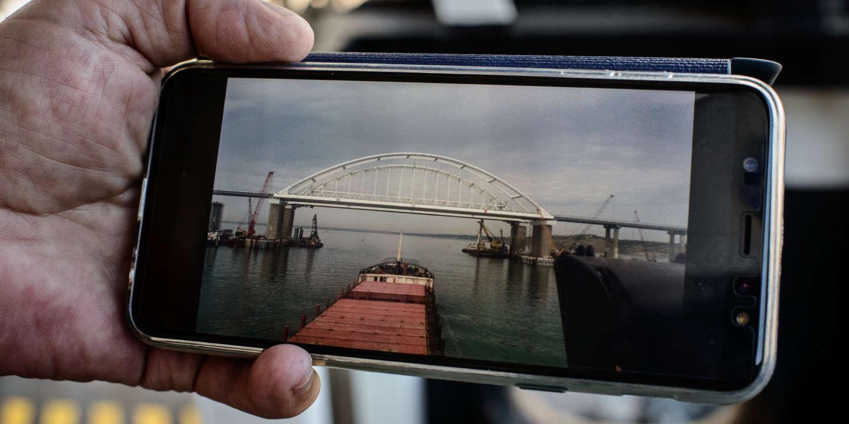 Le capitaine Igor Zavialiov du cargo Salvinia montre des photos du pont entre la russie et la crimée traversant la mer d'Azov. Marioupol. Ukraine.