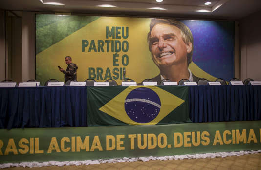 Un journaliste regarde une intervention de Jair Bolsonaro sur Facebook, dans la salle de réunion d'un hôtel où sa conférence de presse a été annulée, dimanche 7 octobre, à Rio de Janeiro.