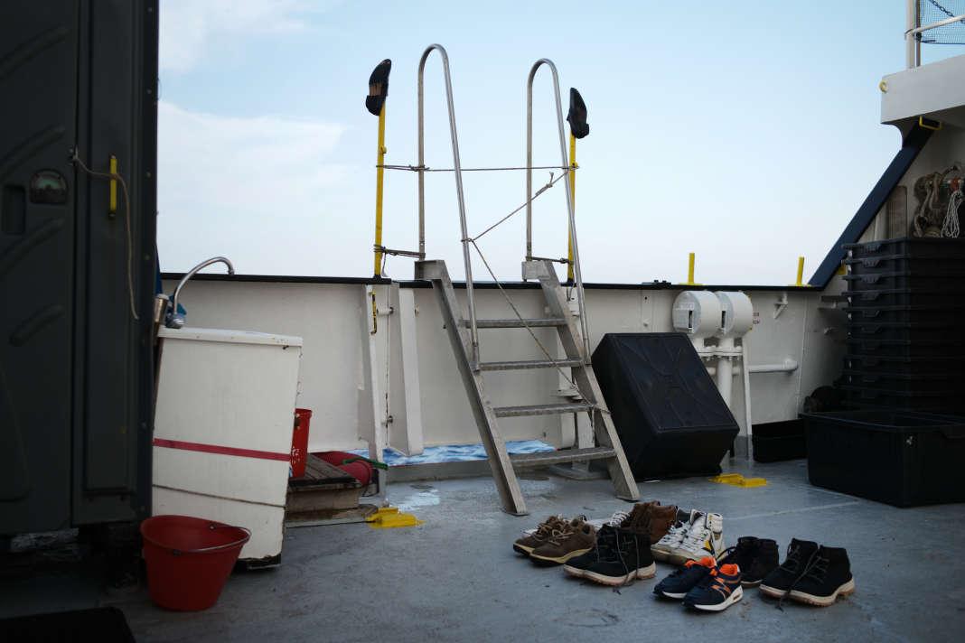 Les chaussures trempées de rescapés sèchent sur un pont du navire, le 20 septembre. SAMUEL GRATACAP POUR LE MONDE