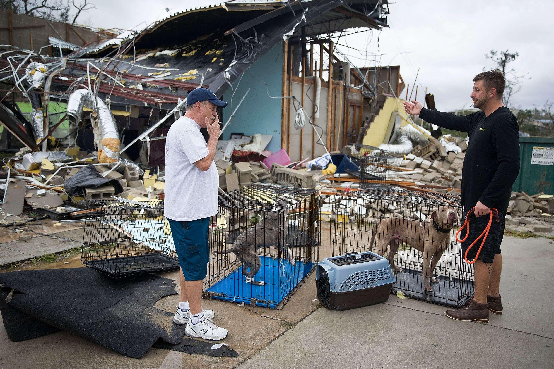 Rick Teska (à gauche) aide un commerçant à secourir ses chiens devant un magasin détruit par la force du cyclone, à Panama City, le 10 octobre.