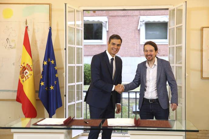 Le chef du gouvernement espagnol Pedro Sanchez (Parti socialiste ouvrier espagnol, à gauche) sert la main de Pablo Iglesias, le chef de file de la gauche radicale, au Palais Moncloa à Madrid, le 11 octobre.