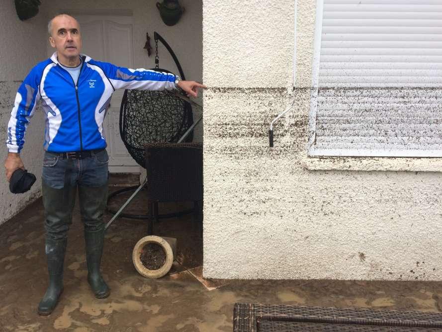 Un résident montre le niveau atteint par l'eau lors des inondations à Villegailhenc, près de Carcassonne, dans le sud de la France.Le niveau atteint lundi matin par la crue à Trèbes, dans la vallée de l'Aude, est sans précédent depuis 1891, c'est-à-dire «pas loin de sept mètres», a déclaré à l'AFP le service Vigicrues.