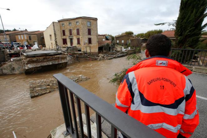 Un policier près d'un pont détruit par les inondations à Villegailhenc, le 15 octobre 2018.