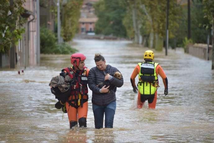 Des habitants de Trèbes, près de Carcassonne, dans l'Aude, sont évacués par les pompiers, lundi 15 octobre 2018.
