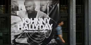 Un piéton passe devant la pochette de l'album posthume de Johnny Hallyday à Paris, le 15 octobre 2018.