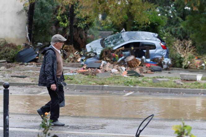 Mardi 16 octobre, un homme marche dans les rues dévastées par les inondations survenues, dans l'Aude, comme ici, à Conques-sur-Orbiel.