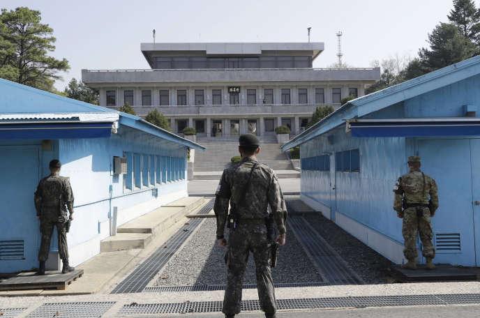 Deux soldats sud-coréens (à gauche et au centre) et un soldat américain (à droite) se tiennent à la frontière entre les deux corées, dans le village de Panmunjom le 18 avril.