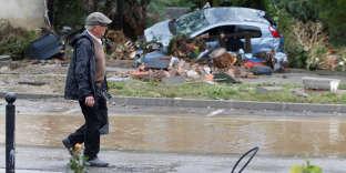 Mardi 16 octobre, un homme marche dans les rues dévastées par les inondations survenues, dans l'Aude, comme ici, à Conques.