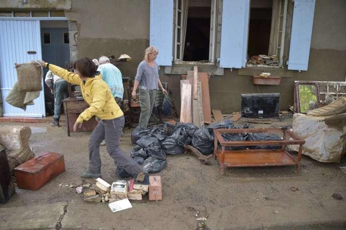 Des habitants de Villegailhenc vident une maison inondée, le 15 octobre.