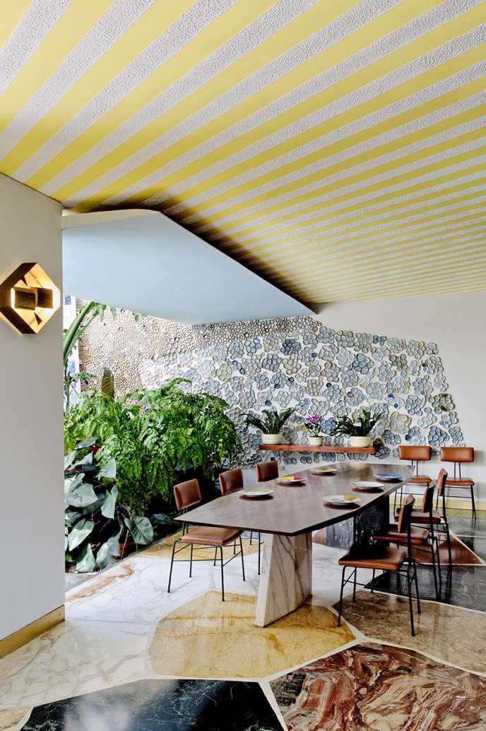 Plafond rayé de jaune, kaléidoscope de marbre, motifs géométriques au mur, mobilier sculptural : telle est la salle à manger d'extérieur de la villa Planchart à Caracas (1957).