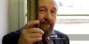 le géographe français Yves Lacoste pose près de la chaise à porteurs du navigateur La Pérouse, le 22 mars 2001, à la Société de Géographie de Paris.