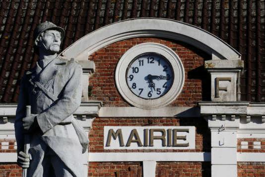 Statue du sclupteur Jules Delvienne dite«l'eveil» à la mairie deGouzeaucourt (Nord) avec l'horloge indiquant 5 h 15, heure de la déclaration de l'armistice le 11 novembre 1918.