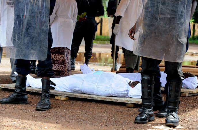 Des policiers guinéens, le 2 octobre 2009, devant les corps de victimes de la répression menée le 28septembre à Conakry par la junte alors au pouvoir.