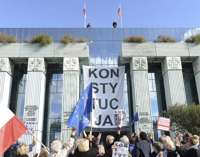 Des manifestants se rassemblent sous une banderole portant le mot « Constitution », devant la Cour suprême, à Varsovie, le 8 octobre.