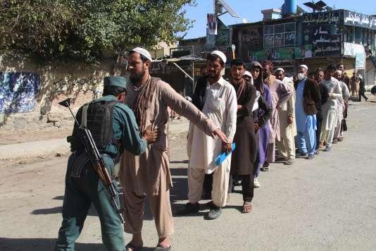 Un policier fouille les électeurs qui se présentent à un bureau de vote, dans la province afghane de Khost, le 20 octobre.