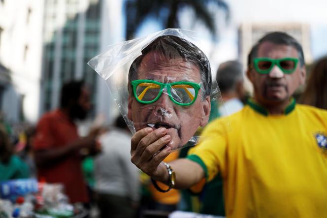 Un vendeur de rue tend un masque représentant le candidat d'extrême droite à la présidentielle brésilienne, Jair Bolsonaro, à Sao Paulo, le 21 octobre.