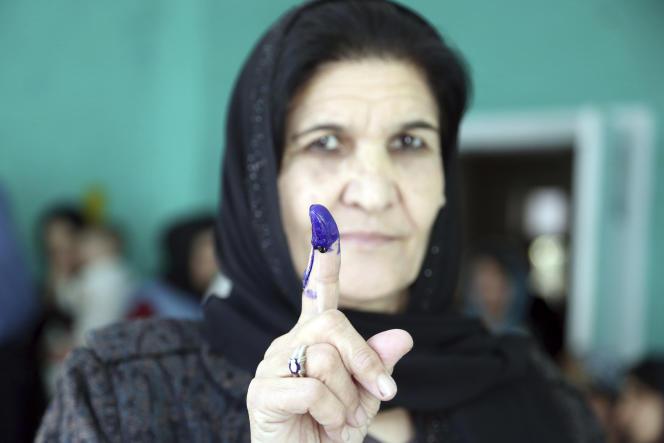 Une femme afghane montre après avoir voté son doigt couvert d'encre indélébile, à Kaboul, le 20 octobre. )