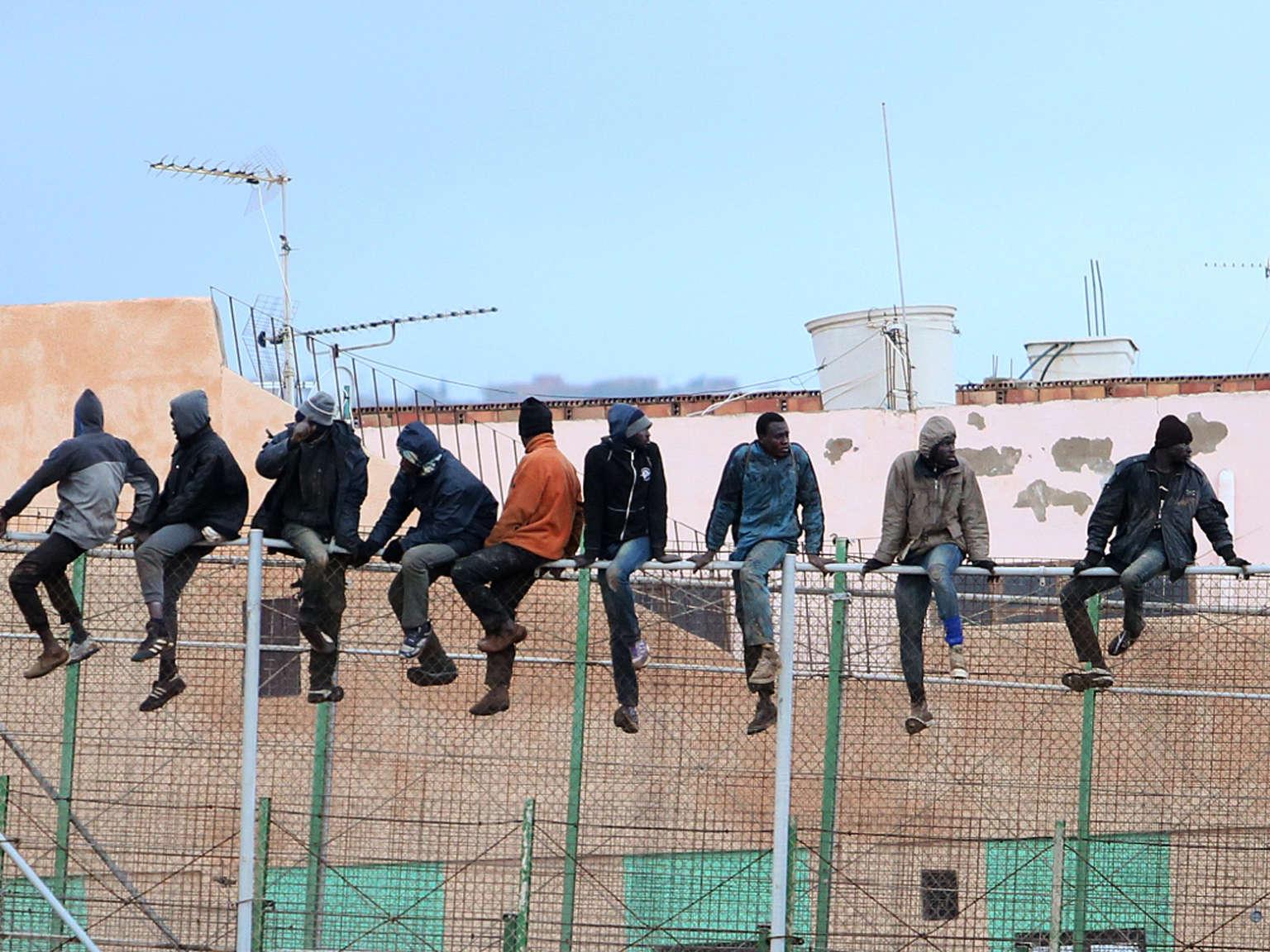 Des migrants sont assis au sommet d'un clôture à la frontière entre le Maroc et l'enclave espagnole de Mellila, en 2015.