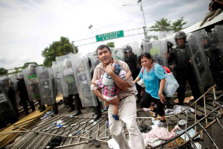 Un homme protège son enfant à Hidalgo, une ville à la frontière entre le Guatemala et le Mexique. Jeudi 18 octobre, les autorités mexicaines étaient parvenues àbloquer la caravane.
