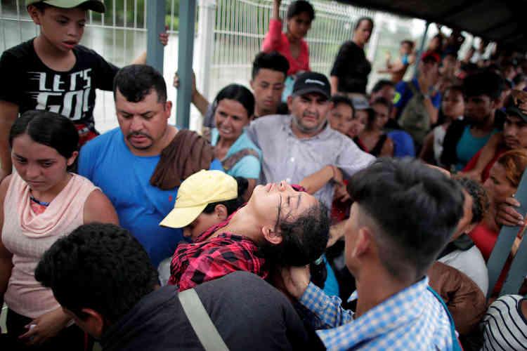 Une femme fait un malaise sur le pont d'Hidalgo. Sous la chaleur et sans beaucoup d'eau, des migrants honduriens attendent afin de déposer une demande d'asile au Mexique pour continuer leur voyage vers les Etats-Unis.