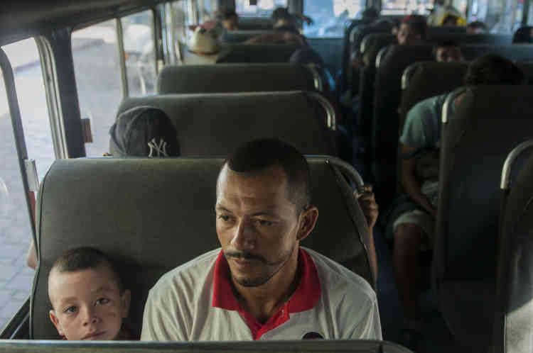 Epuisés par la marche sous la chaleur et avec très peu d'eau, des migrants honduriens font demi-tour en empruntant des bus de la police guatemaltèque qui les ramènent à la frontière hondurienne, le 21 octobre.