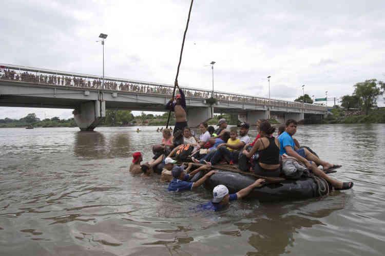 Face à la frontière fermée sur le pont d'Hidalgo, entre le Mexique et le Guatemala, un groupe de migrants honduriens traverse le Suchiate à l'aide d'un radeau de fortune pour entrer illégalement au Mexique, le 20 octobre.
