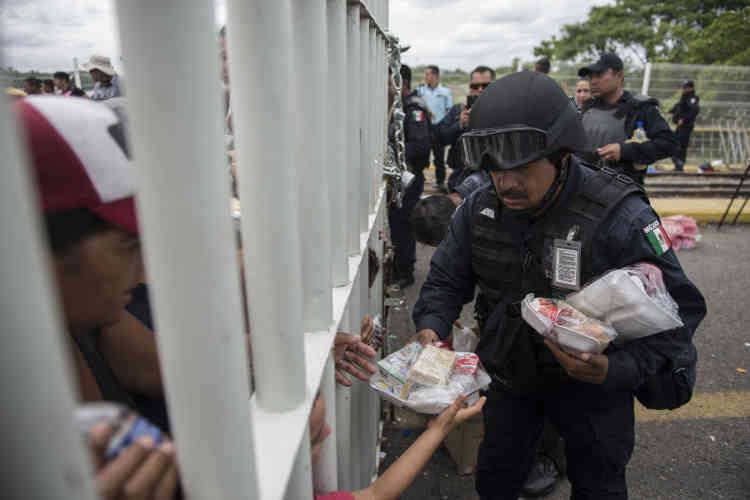Un policier mexicain distribue des repas aux migrants sur le pont d'Hidalgo le 20 octobre.Donald Trump a rappelé par un tweet que les migrants qui voulaient entrer aux Etats-Unis devait d'abord faire une demande d'asile au Mexique (le 20 octobre).