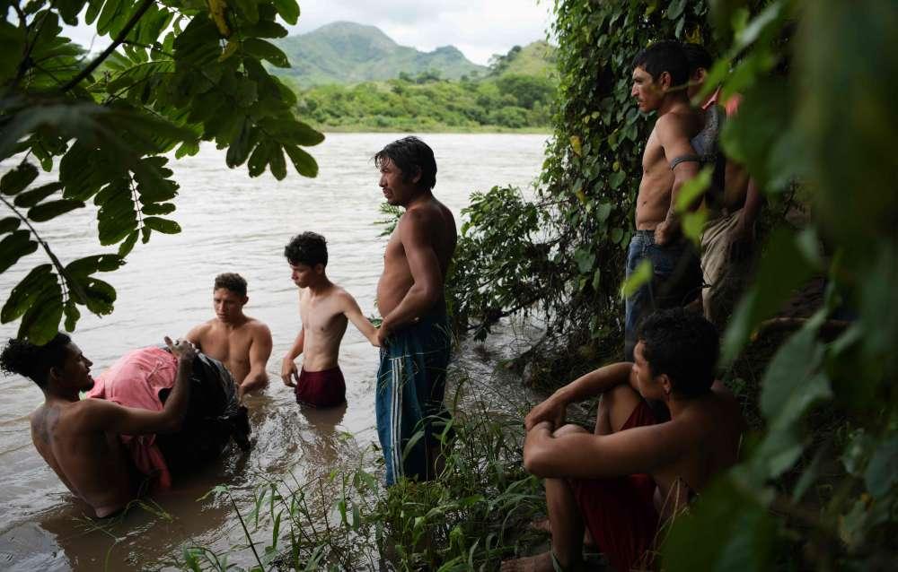 Des migrants honduriens se préparent à traverser la Goascorán, le 18 octobre, afin d'entrer illégalement au Salvador et de rejoindre la caravane de migrants qui se dirige vers les Etats-Unis.
