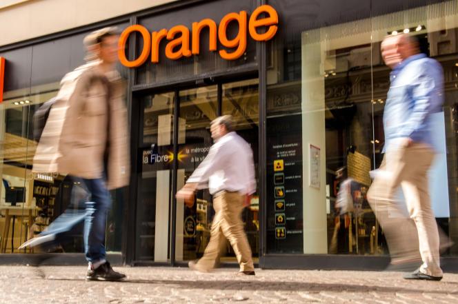 Des personnes passent devant une boutique Orange, à Lille, le 23 septembre 2016.