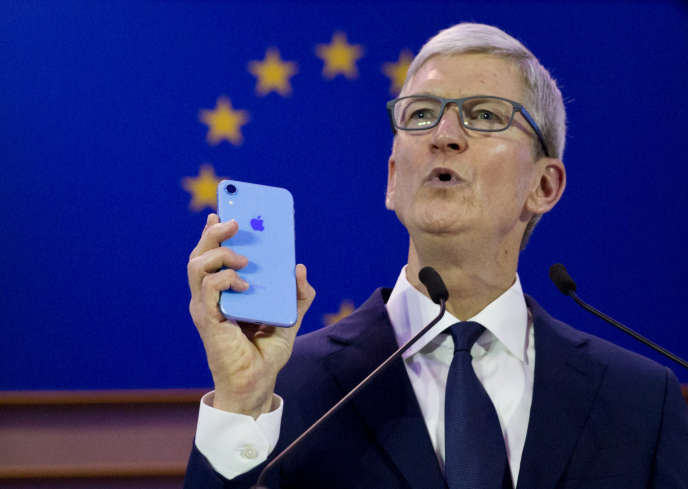 Le patron d'Apple Tim Cook brandit un iPhone, mercredi 24 octobre à Bruxelles.