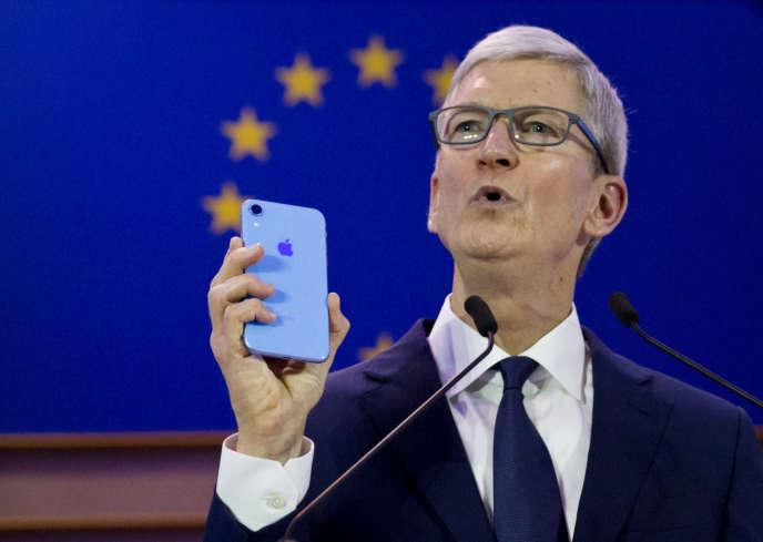 Le patron d'Apple Tim Cook brandit un iPhone, mercredi 24 octobre à Bruxelles.