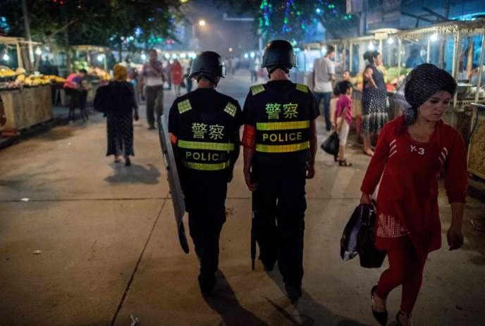 Une patrouille de police sur le marché de nuit de Kashgar, dans la province du Xinjiang, en territoire ouïgour.